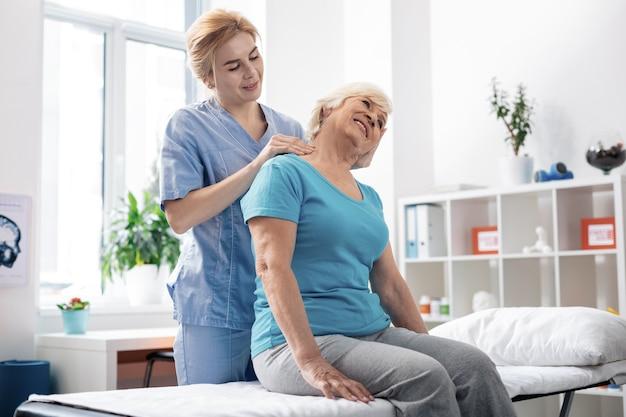 Mantenerse saludable. agradable mujer de pelo gris recibiendo masaje de cuello mientras visita el hospital