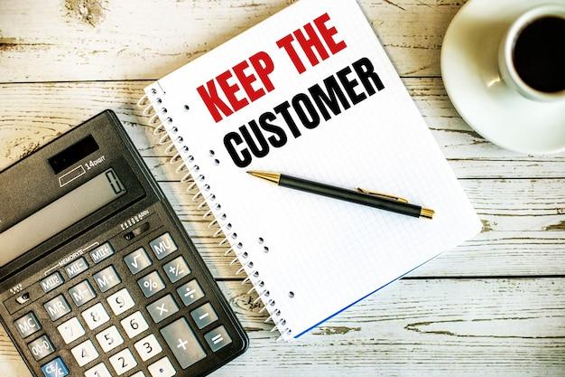 Mantenga al cliente escrito en papel blanco cerca del café y la calculadora en una mesa de madera clara