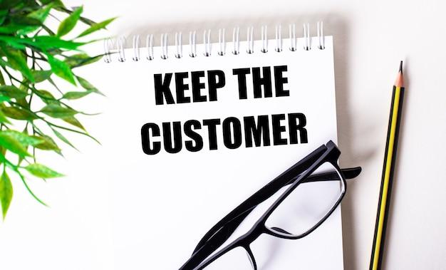 Mantenga al cliente escrito en papel blanco sobre un fondo marrón claro.