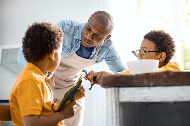 Mantenga la calma. padre joven cariñoso que pide a sus hijos que se porten bien mientras juegan con dinosaurios de juguete demasiado fuerte durante el desayuno