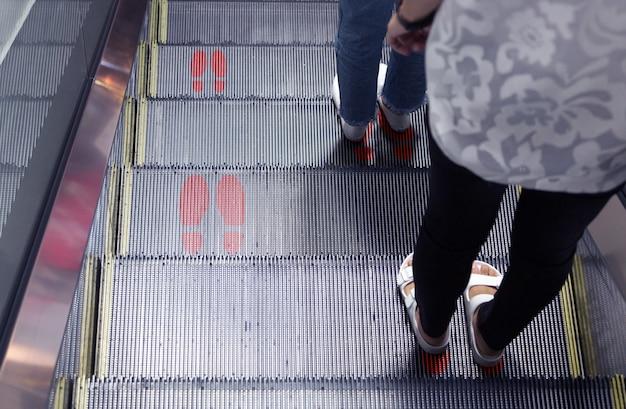 Mantenga el distanciamiento en la escalera mecánica en el comercio moderno para proteger la pandemia