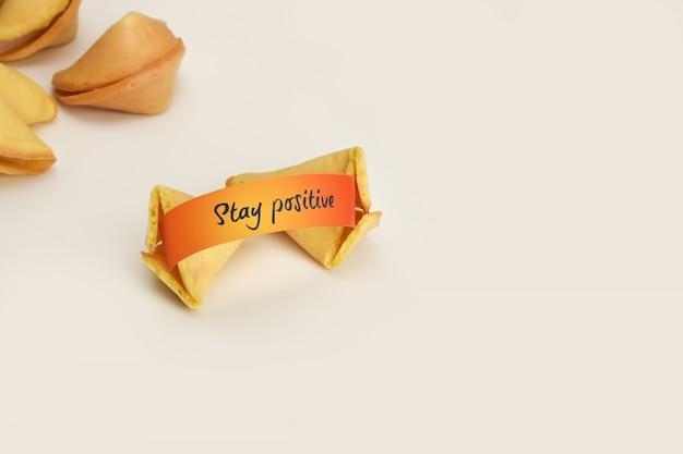 Manténgase positivo en papel de deseos de naranja en galleta de la fortuna china sobre fondo blanco.