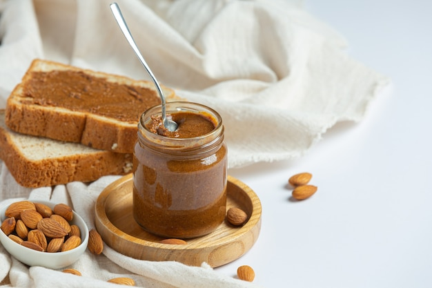 Mantequilla de almendra orgánica cruda sobre fondo blanco.