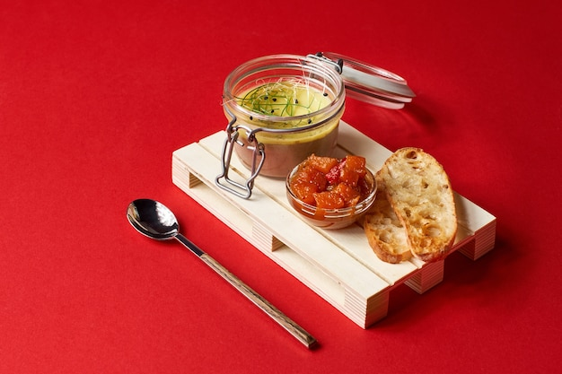 Mantequilla de calabaza en frasco de vidrio con palitos de canela y azúcar en la pared roja, enfoque selectivo
