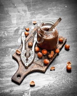 Mantequilla de chocolate con avellanas en una pizarra negra