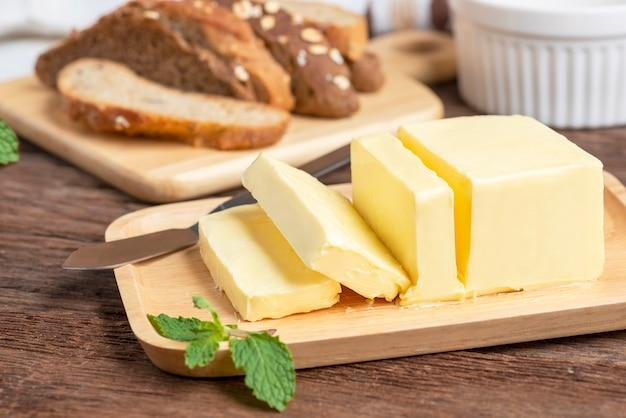 Mantequilla fresca cortada con cuchillo en placa de madera y pan.