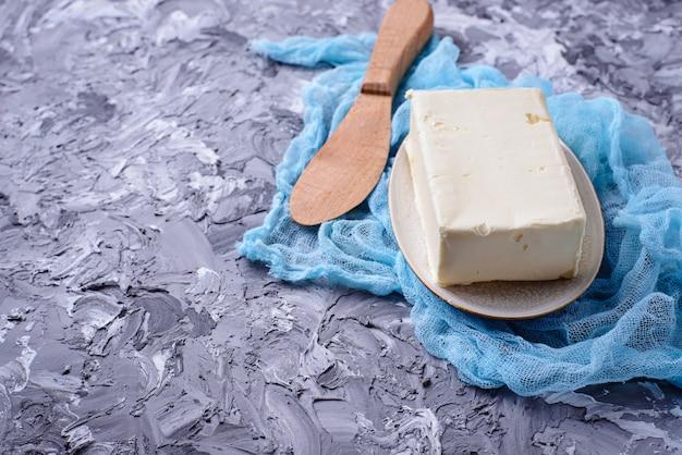 Mantequilla fresca y cuchillo sobre fondo concreto