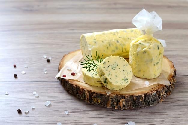 Mantequilla con una hierba para sándwiches y bistec. porción de mantequilla de hierbas en rodajas sobre una tabla de madera. comida italiana casera. enfoque selectivo.