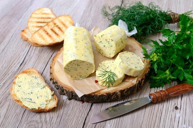 Mantequilla con una hierba para sándwiches y bistec. porción de mantequilla de hierbas en rodajas sobre una tabla de madera. comida italiana casera.