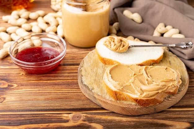 Mantequilla de maní en una cuchara cerca de una pasta de maní cremosa en un frasco de vidrio abierto, una rebanada de pan tostado de mantequilla de maní y mermelada.