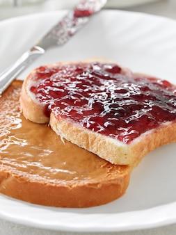Mantequilla de maní y mermelada en trozos de pan.