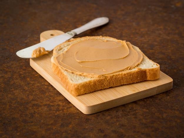 Mantequilla de maní en tostada. fondo oscuro de metal oxidado viejo, vista lateral, enfoque selectivo