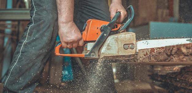 Manual de motosierra en manos de un carpintero cortando madera