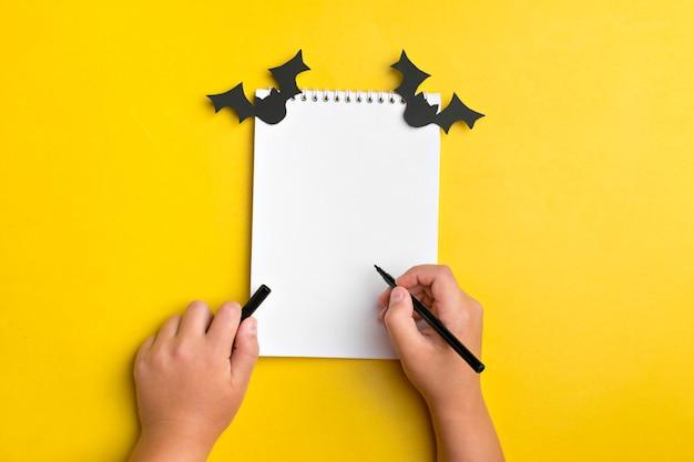 Manualidades para fiesta de halloween. cuaderno blanco, murciélagos de papel negro, niño sostiene bolígrafo