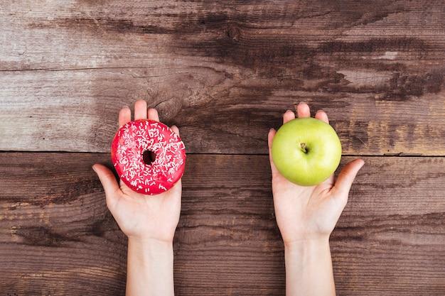 Manzana y donut sobre fondo de madera