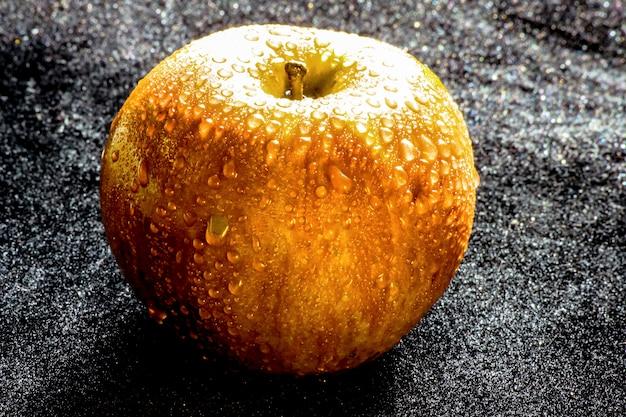 Manzana dorada en el negro texure