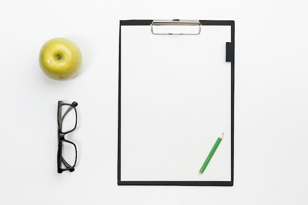 Manzana entera verde con lentes y lápiz verde en el portapapeles blanco sobre el escritorio de oficina blanco