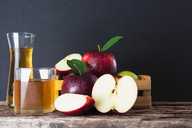 Manzana fresca en caja de madera con jugo de manzana sobre negro, fruta fresca y producto de jugo