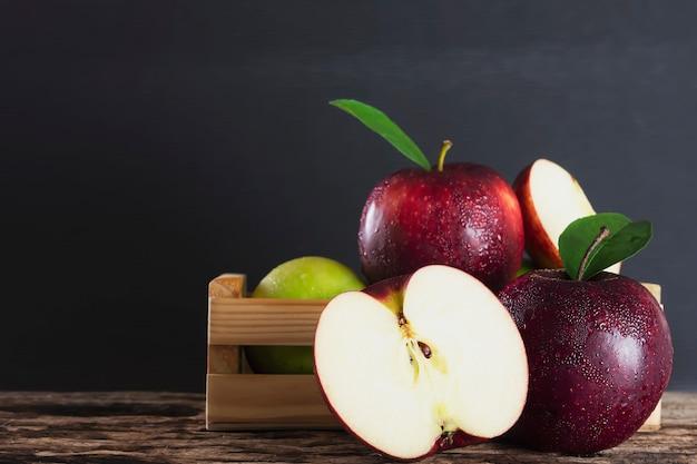 Manzana fresca en caja de madera sobre fruta negra y fresca