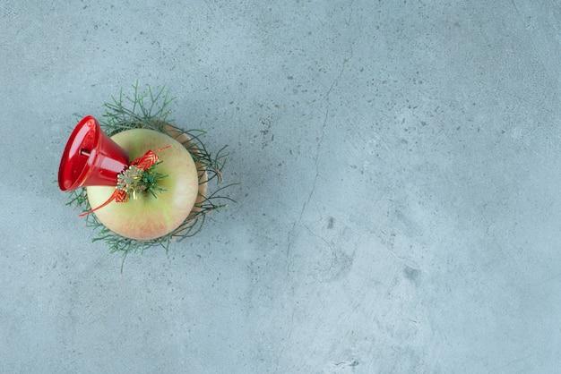 Una manzana fresca con campana de navidad roja sobre mármol.