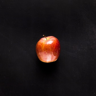 Manzana fresca en escritorio negro