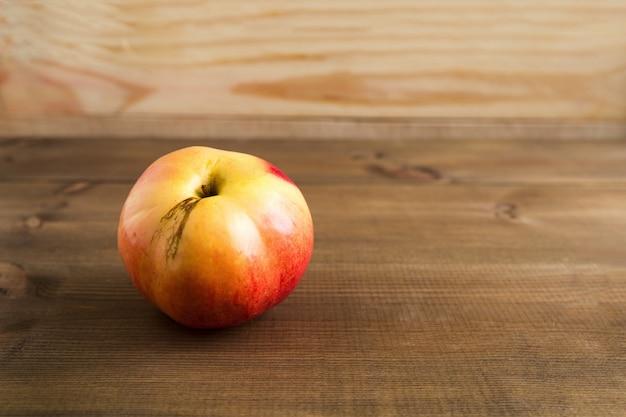 Manzana grande imperfecta, fea, con defectos en la piel sobre el fondo marrón de madera de cerca con espacio de copia.