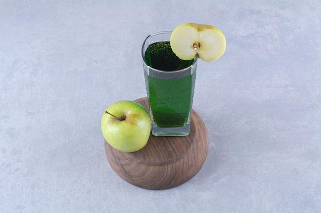 Manzana y jugo en un cuenco invertido, sobre la mesa de mármol.