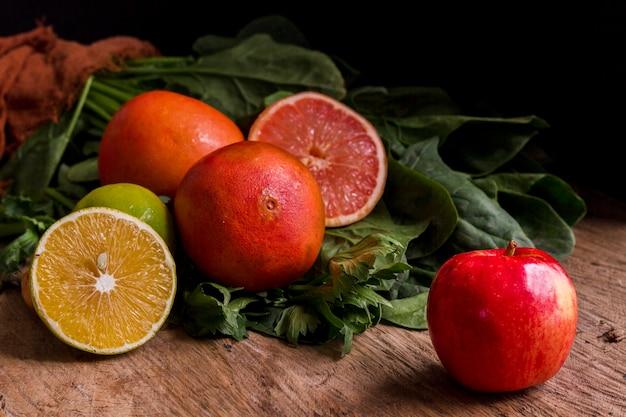 Manzana limón y pomelo en mesa de madera