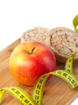 Manzana, naranja, kiwi con cinta métrica sobre fondo blanco, dieta saludable.