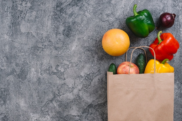 Manzana; naranja y verduras derramadas de una bolsa de papel sobre fondo de hormigón