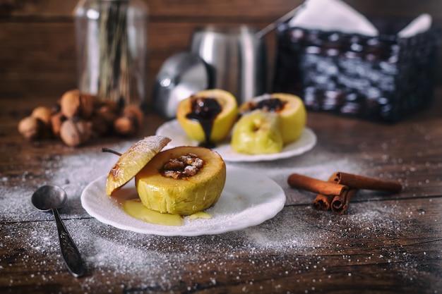 Manzana rellena al horno con nueces, miel y chocolate en platos de postre blanco, fondo de madera oscura. navidad dulce concepto de alimentación saludable