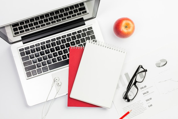 Manzana roja, audífonos, computadora portátil, bloc de notas en espiral y anteojos en plan de presupuesto sobre fondo blanco