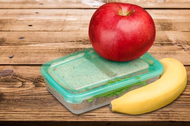 Manzana roja con banano y caja de comida para la escuela.