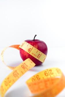 Manzana roja con cinta métrica en mesa blanca