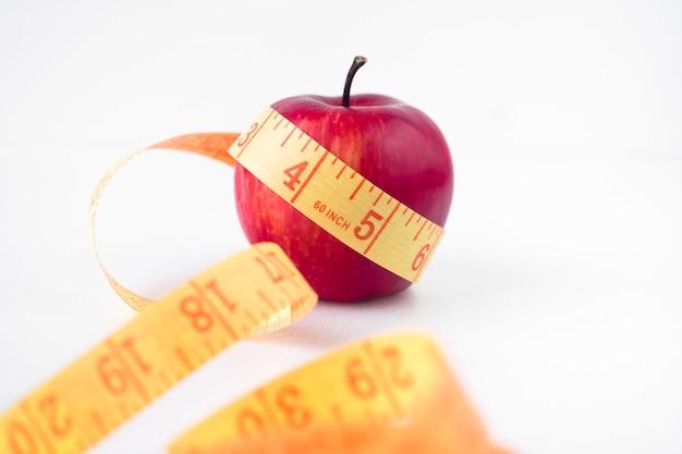 Manzana roja con cinta métrica en la mesa