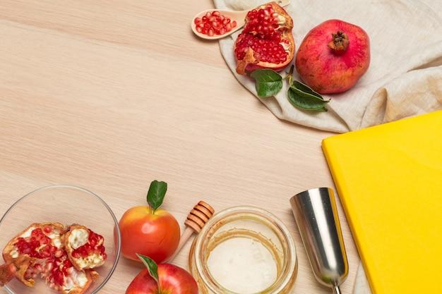Manzana roja, granada y tarro de miel para el año nuevo judío sobre tabla de madera