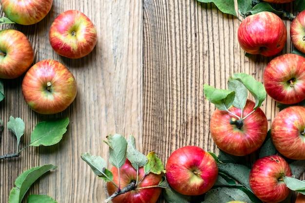 Manzana roja y hojas sobre mesa de madera