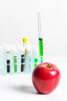 Manzana roja y jeringa con productos químicos verdes
