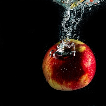 Manzana roja madura cae al agua con salpicaduras