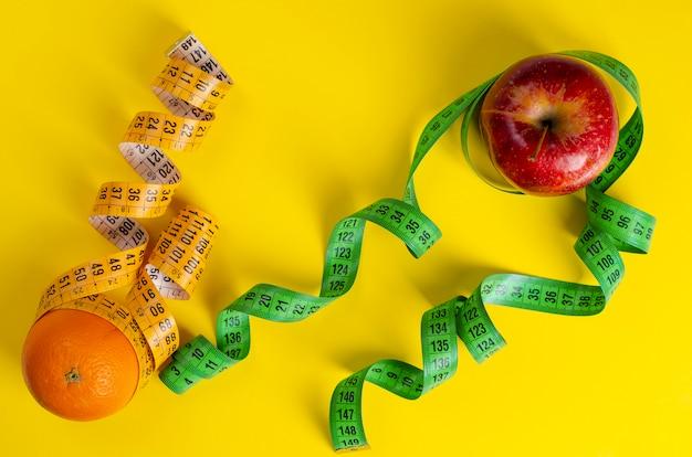 Manzana roja y naranja con cintas de medir en amarillo.