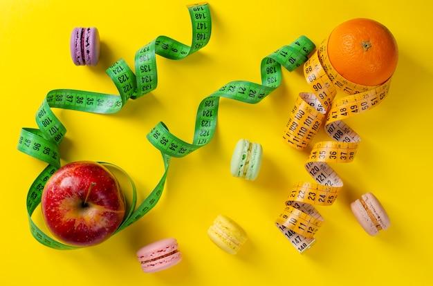 Manzana roja y naranja con cintas de medir y macarrones franceses dulces en amarillo
