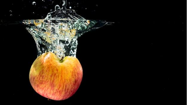 La manzana roja partida en dos caer en el chapoteo del agua en fondo negro