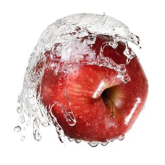 Manzana roja en salpicaduras de agua aislado sobre fondo blanco.