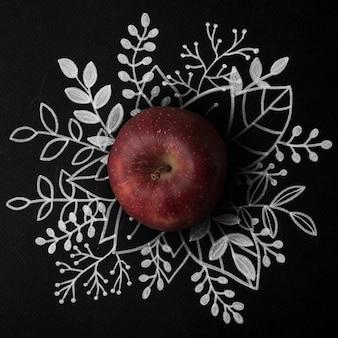 Manzana roja sobre contorno floral dibujado a mano