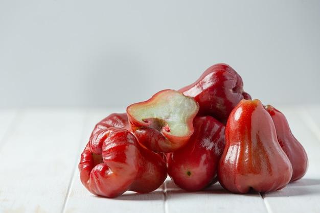 Manzana rosa sobre superficie de madera blanca