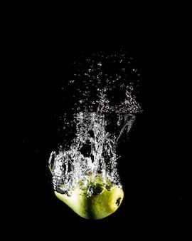 Manzana sumergiéndose en el agua