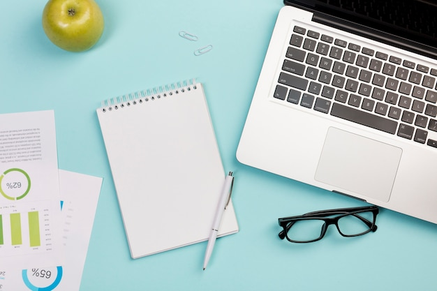 Manzana verde, bloc de notas en espiral, bolígrafo, lentes y computadora portátil sobre fondo azul
