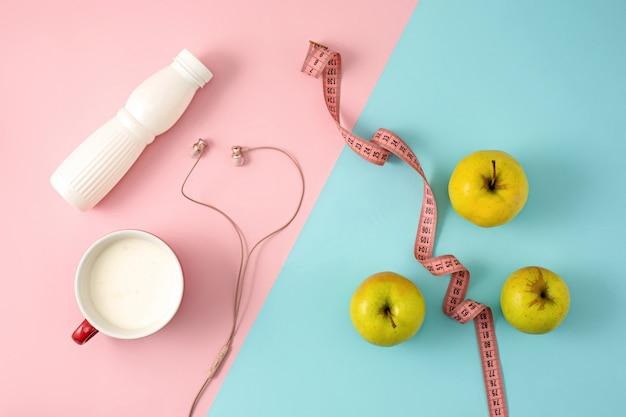 La manzana verde y la botella de yogurt con cinta métrica
