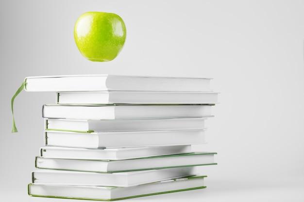 Una manzana verde se cierne sobre libros aislados sobre una mesa blanca.