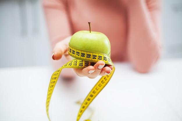 Manzana verde y cinta de centímetro en manos femeninas
